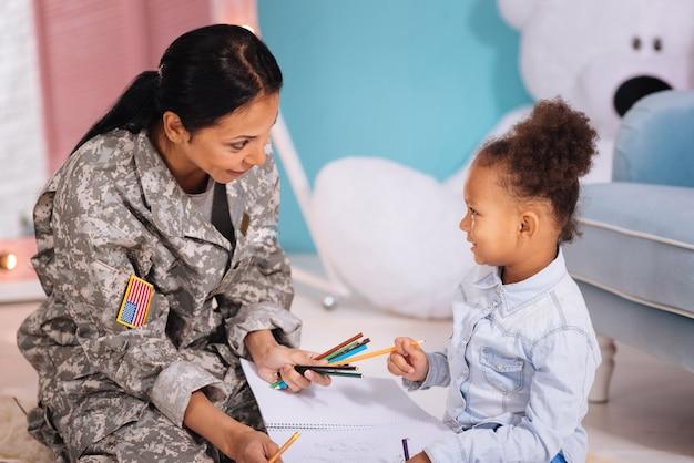 O que você prefere. mãe adorável, emocional e alegre perguntando à filha sobre suas preferências enquanto passam o tempo em casa e brincam juntas no quarto