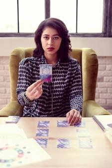 O que você vê. linda mulher morena pegando um cartão da mesa enquanto o mostro para você