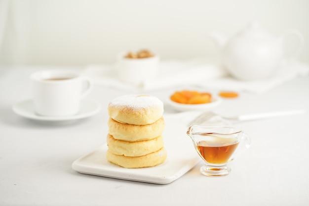 O queijo fritado endurece, panquecas doces do queijo na placa branca no fundo branco. festa do chá em casa