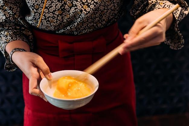 O quimono vestindo da mulher está batendo o ovo de galinha com os chopsticks mergulhando com carne de sukiyaki.