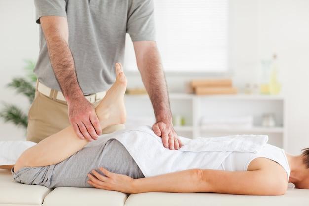 O quiroprático alonga a perna de uma mulher