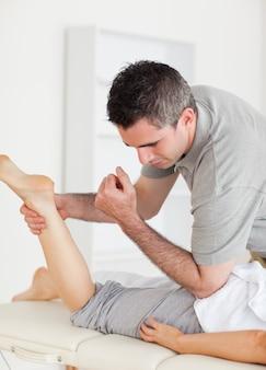 O quiroprático alonga a perna do cliente feminino