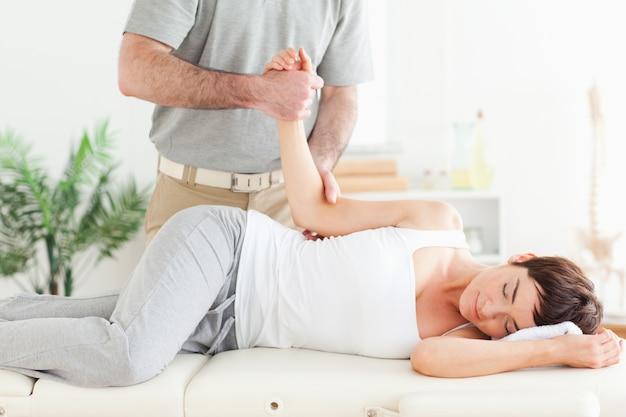 O quiroprático alonga o braço de uma mulher