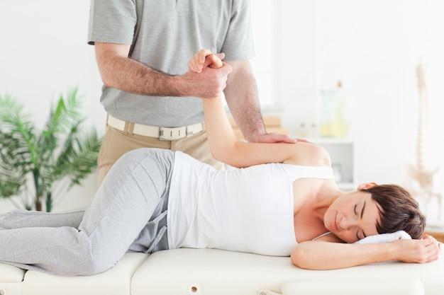 O quiroprático alonga o braço do cliente feminino