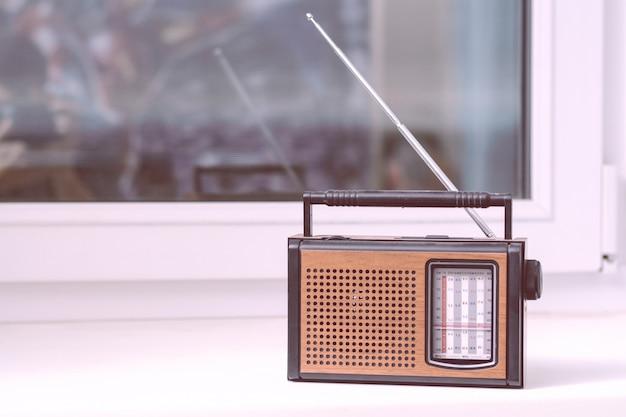 O rádio retrô marrom velho está no peitoril da janela branca da sala da antena direcional