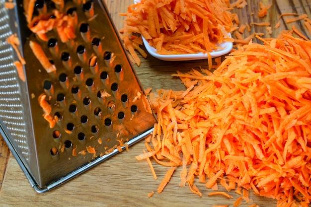 O ralador do metal e a pilha de cenouras raspadas encontram-se na tabela de madeira. cozinhar comida vegetariana saborosa.