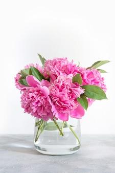 O ramalhete da peônia cor-de-rosa floresce como o quadro no rosa pastel. copie o espaço para o texto. vista do topo. lay plana.