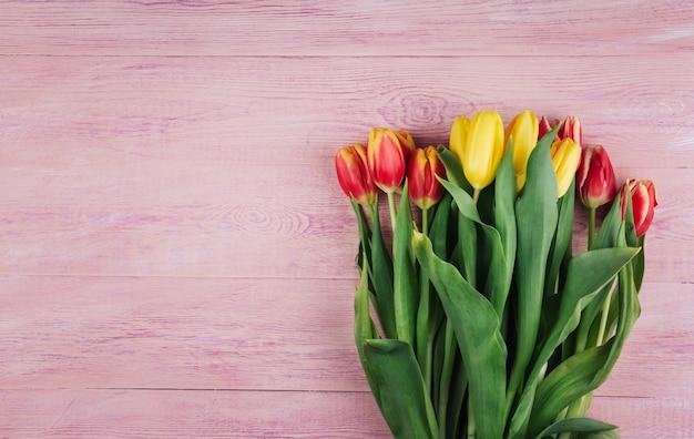 O ramalhete de tulipas amarelas, vermelhas e cor-de-rosa em um fundo de madeira cor-de-rosa copia o espaço.