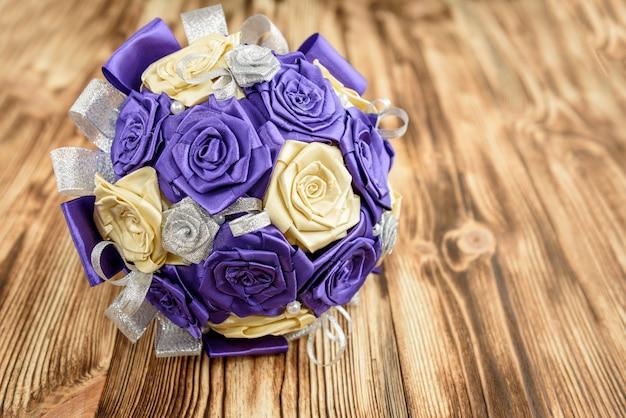 O ramalhete nupcial do casamento de rosas artificiais roxas, bege e prata floresce das fitas de cetim na tabela de madeira com espaço da cópia.