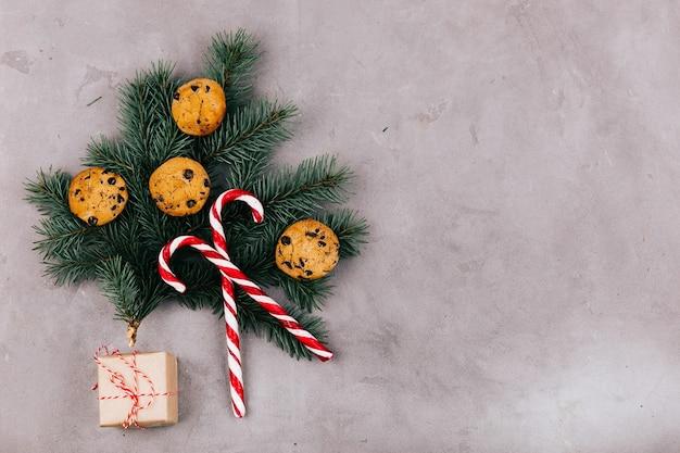 O ramo de abeto com biscoitos, doces brancos vermelhos e caixa presente encontra-se em fundo cinza