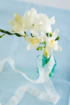 O ramo de freesia branca com flores e botões em garrafas decorativas