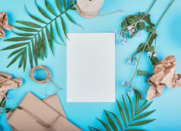 O ramo de palma, as caixas de presente e a juta corda corda em um fundo azul, estilo do verão.