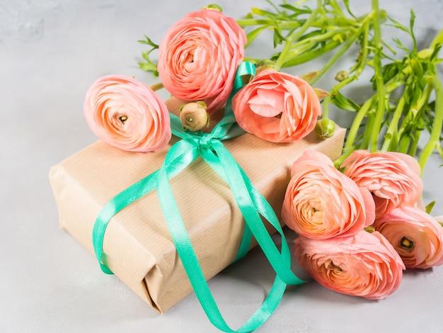 O ranúnculo cor-de-rosa bonito floresce o ramalhete e a caixa de presente. dia das mães dos namorados. presente de aniversário de casamento