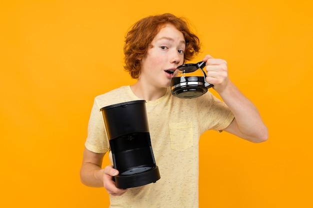 O rapaz adolescente com uma máquina de café bebe café de uma caneca de vidro em um fundo amarelo