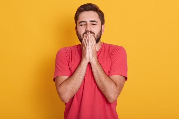 O rapaz bonito jovem de estúdio com olhos fechados espera por fortuna e boa sorte, carrinhos vestindo camiseta casual vermelha, mantém as mãos em gesto de oração, isolado no amarelo.
