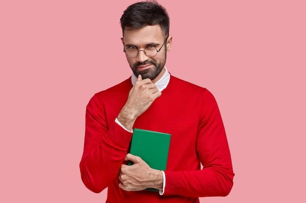O rapaz cunny tem intenção de fazer algo, segura o queixo, carrega um caderno verde para escrever notas, usa um suéter vermelho, óculos ópticos