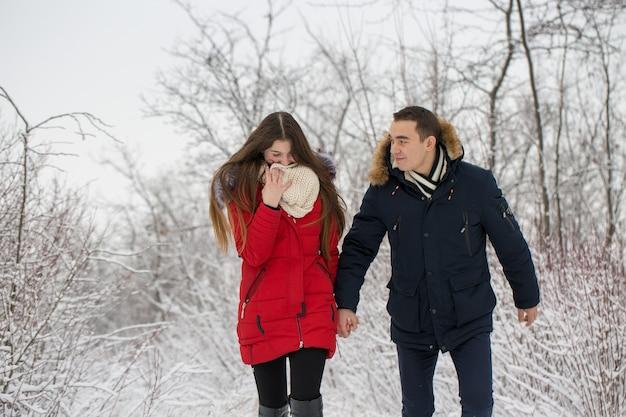 O rapaz e a rapariga descansam na floresta de inverno marido e mulher na neve casal jovem