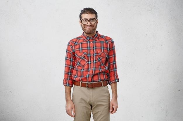 O rapaz engraçado de óculos com lentes grossas, vestido formalmente, tem uma expressão alegre
