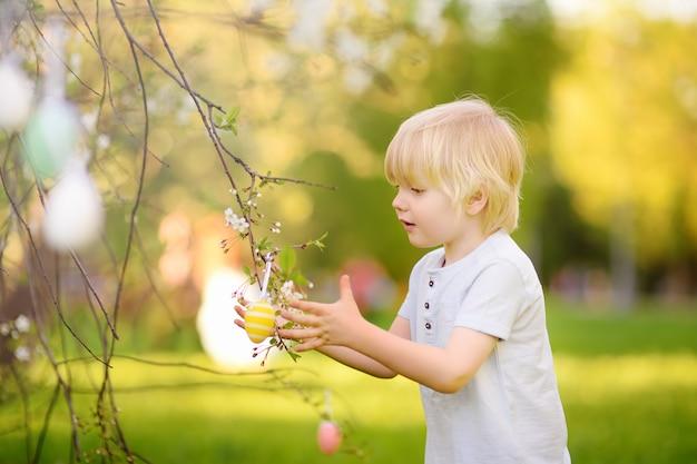 O rapaz pequeno bonito caça para o ovo da páscoa na árvore de florescência do ramo.