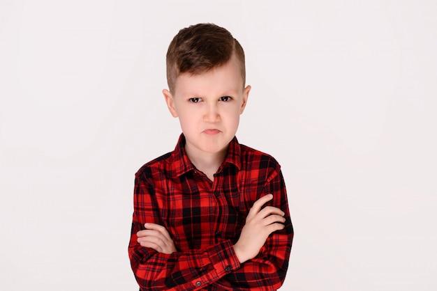 O rapaz pequeno com emoção expressivo em um fundo branco.