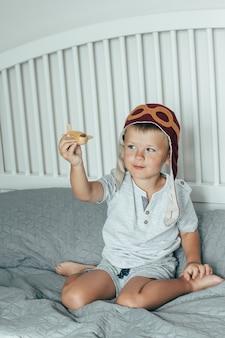 O rapaz pequeno de sorriso bonito no tampão do piloto joga na cama com um plano de madeira pequeno. dia da aviação.