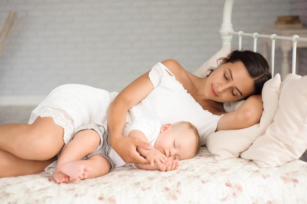 O rapaz pequeno encontra-se perto de sua mamã que descansa na cama.