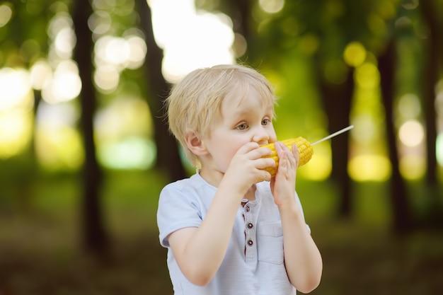 O rapaz pequeno está comendo o milho ao ar livre. comida de rua para crianças.