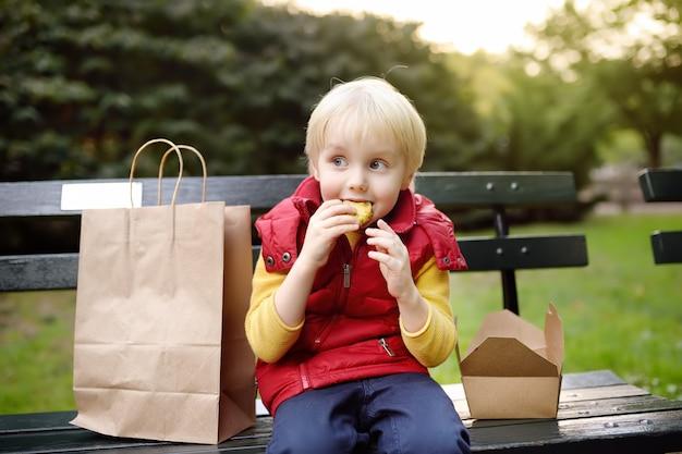 O rapaz pequeno está comendo seu almoço após o jardim de infância. comida de rua para crianças.