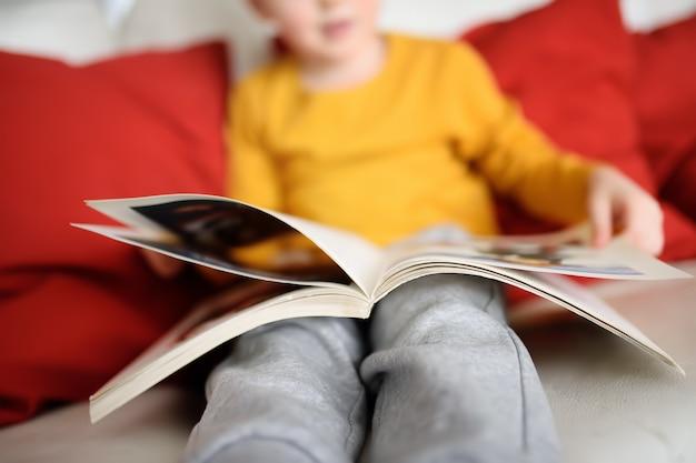 O rapaz pequeno está sentando-se em casa no sofá e está lendo-se um livro. aprendendo a ler.