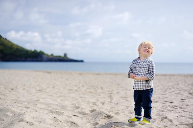 O rapaz pequeno feliz bonito aprecia férias na praia perto do mar tyrrhenian. criança bonito engraçada fazendo férias e curtindo o verão.