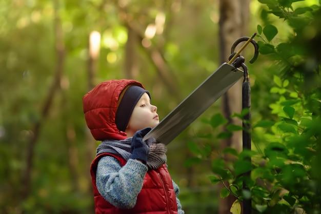 O rapaz pequeno lê um sinal explicativo no jardim zoológico ou no parque da natureza.
