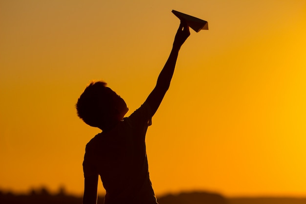 O rapaz pequeno prende um avião de papel em sua mão no por do sol. uma criança levantou a mão para o céu e brinca com origami à noite na rua