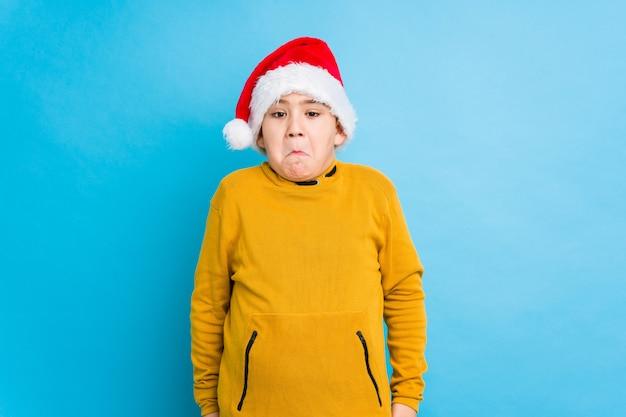O rapaz pequeno que comemora o dia de natal que veste um chapéu de santa isolado encolhe os ombros e abre os olhos confusos.