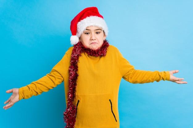 O rapaz pequeno que comemora o dia de natal que veste um chapéu de santa isolou a dúvida e encolher os ombros os ombros em questionar o gesto.