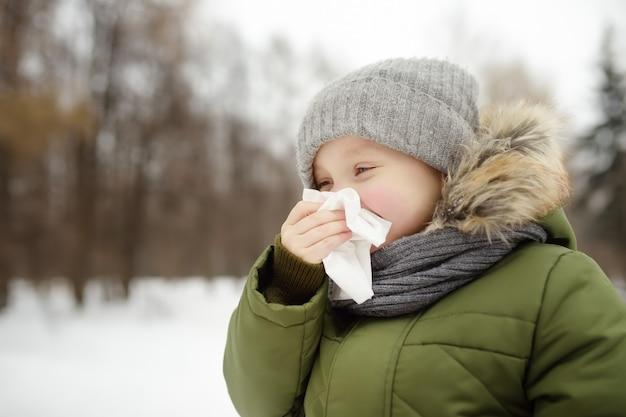 O rapaz pequeno que espirra e limpa o nariz com o guardanapo durante o passeio no parque do inverno. época de gripe e rinite fria. garoto alérgico.