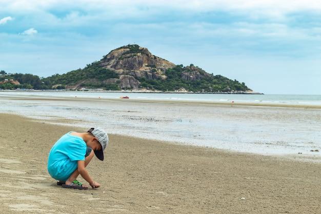 O rapaz sentado na praia de areia