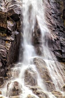 O rápido fluxo de água caindo de um penhasco