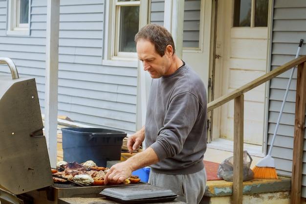 O rasgo da carne de porco da grade que cozinha o marisco do calamar com macio-foco no fundo come o restaurante.