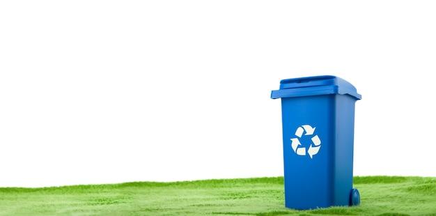 O recipiente de plástico azul fica na grama verde contra um fundo branco