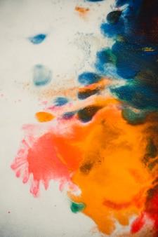 O redemoinho vórtice espalha cores de tinta colorida sobre fundo branco. espalha abstratamente a tinta corante de fundo vermelho, verde, amarelo, laranja, azul no papel. fundo abstrato de arte criativa. fundo colorido