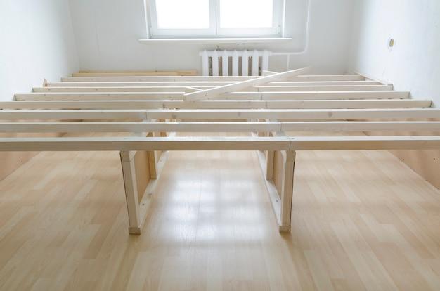 O redesenho funciona dentro de uma sala iluminada com foco na estrutura do piso de madeira
