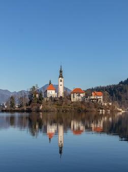 O reflexo de um antigo castelo na água cercado por árvores e montanhas