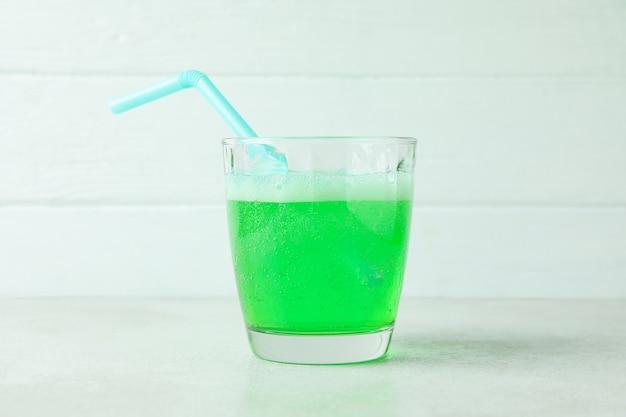 O refrigerante é derramado em um copo contra uma superfície de madeira branca