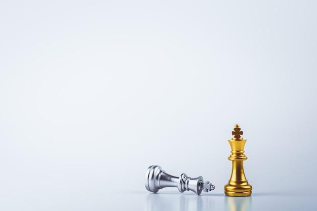 O rei de ouro do xadrez em pé encontra derrotar os inimigos.
