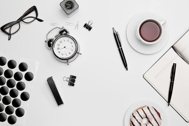 O relógio, caneta e óculos na superfície branca