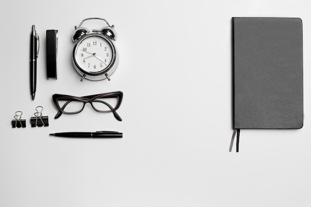 O relógio, caneta e óculos no espaço em branco