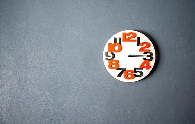 O relógio de parede branco pendurado na parede cinza, apropriado o fundo, idéia cópia espaço