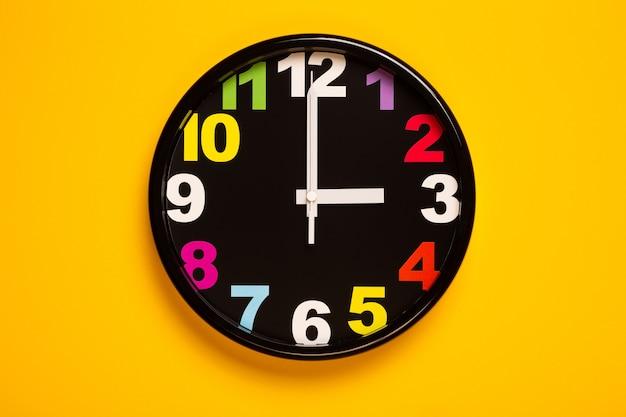 O relógio de parede colorido mostra três horas