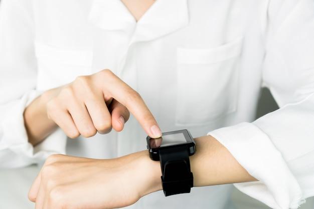O relógio digital da tela de toque da mulher na tecnologia da exposição e da tecnologia avança em uma comunicação.