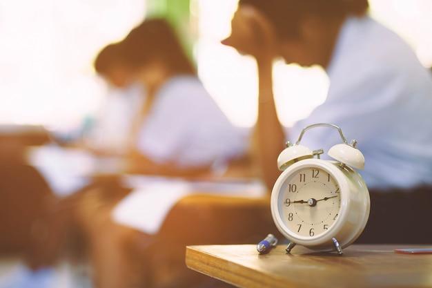 O relógio é usado para ver a hora em que os alunos fazem o exame na sala de aula.